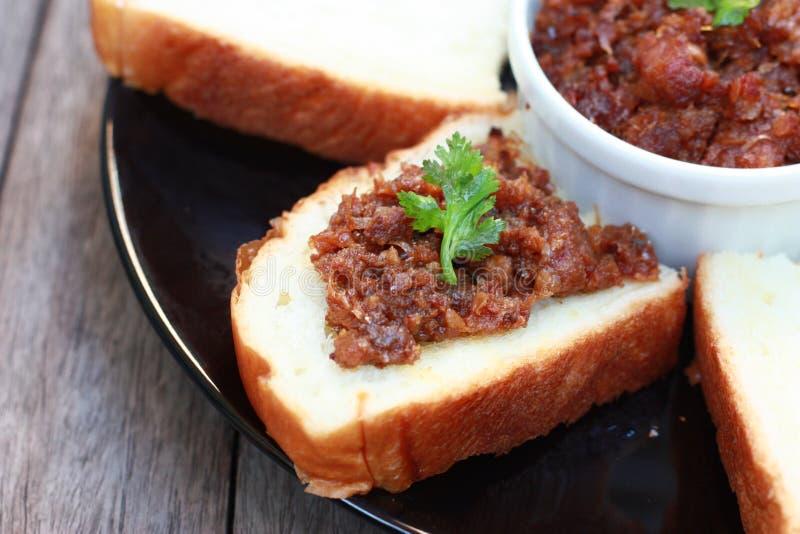 Pâte de piment répandue sur le pain images libres de droits