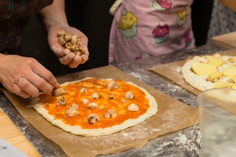 Pâte de pizza avec la sauce tomate Chef féminin ajoutant quelques champignons images stock