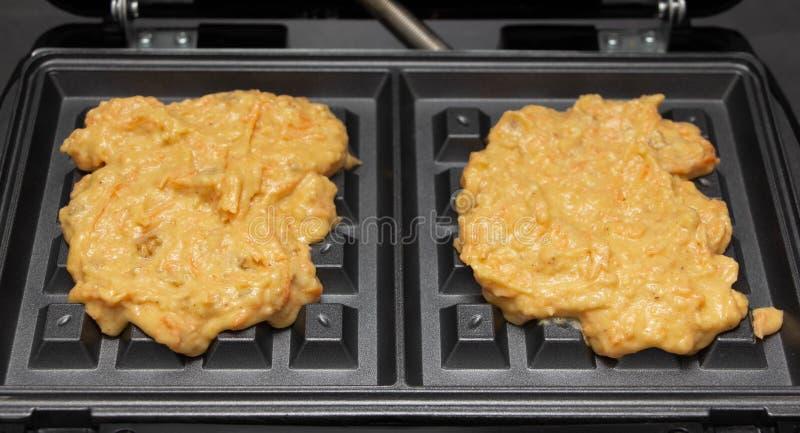 Pâte faite maison pour des gaufres de carotte sur un fer de gaufre photographie stock libre de droits