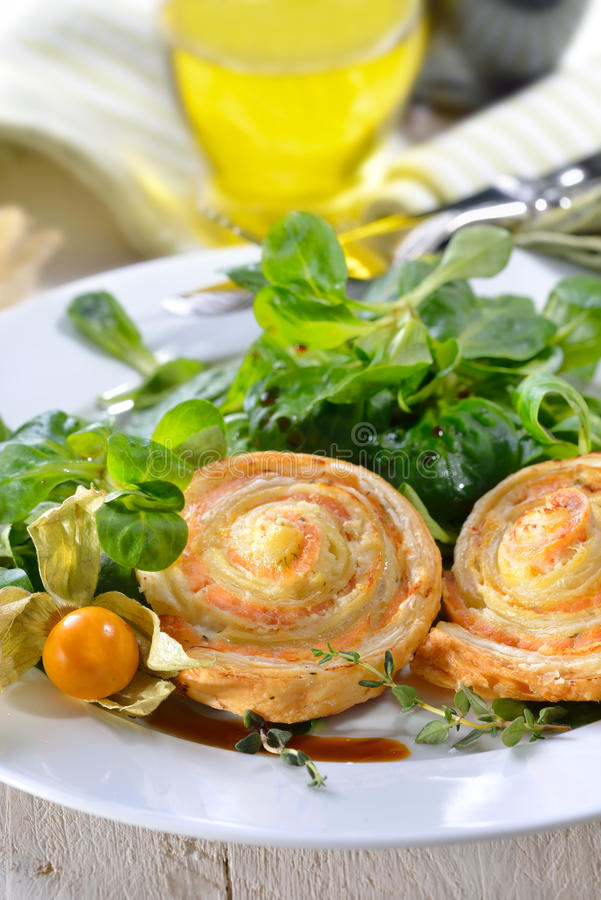 Pâte feuilletée avec des saumons sur la salade images libres de droits