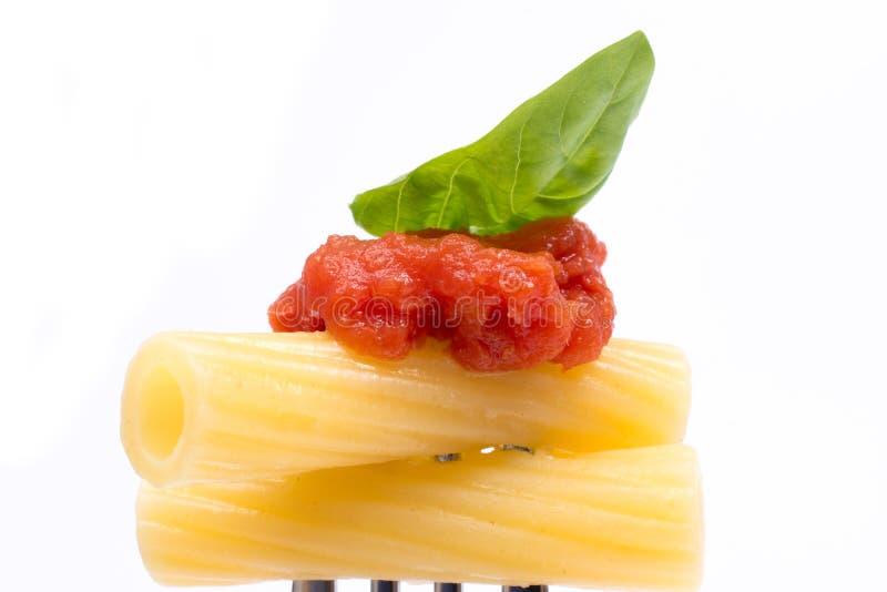 Pâtes à l'arrière-plan blanc Rigatoni, tomate et basilic sur la fourchette Concept italien de cuisine photos stock