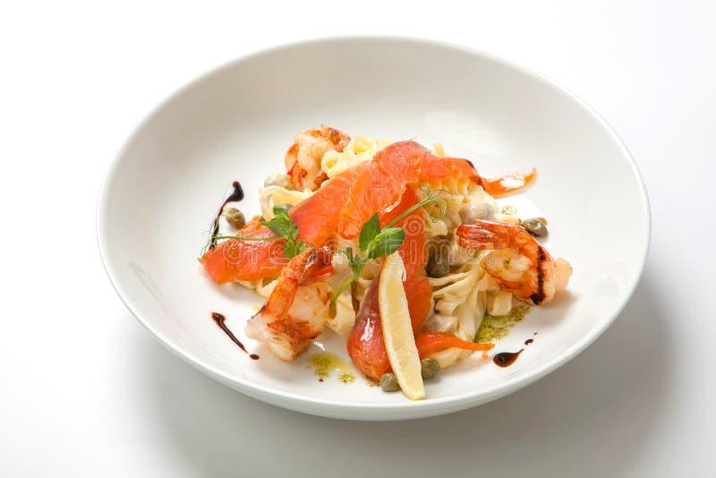 Pâtes avec la crevette et la sauce crémeuse dans un plat profond blanc image libre de droits