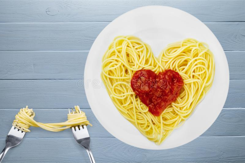Pâtes avec la sauce tomate dans la forme du coeur avec deux photographie stock libre de droits