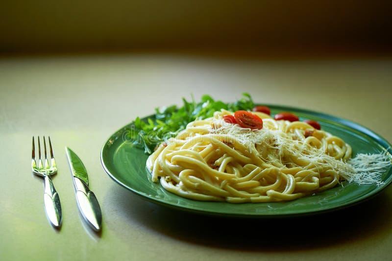 Pâtes Carbonara avec le parmesan râpé et les tomates-cerises, décorés de l'arugula D?jeuner italien images libres de droits