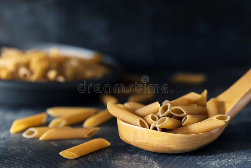 Pâtes complètes au-dessus de nourriture en bois d'obscurité de cuillère image stock