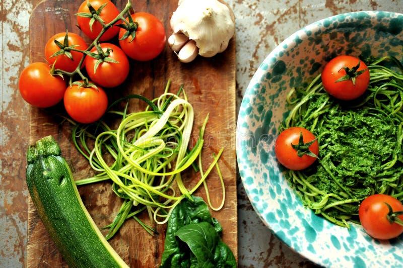 Pâtes crues avec le pesto de courgette et d'épinards avec des tomates image libre de droits