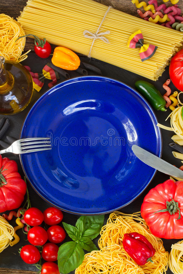 Pâtes crues avec les ingridients et le plat bleu image stock