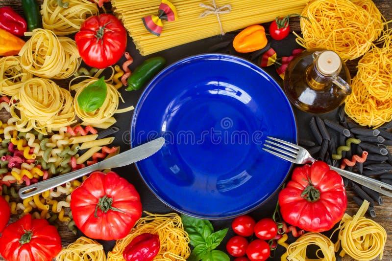 Pâtes crues avec les ingridients et le plat bleu photo libre de droits
