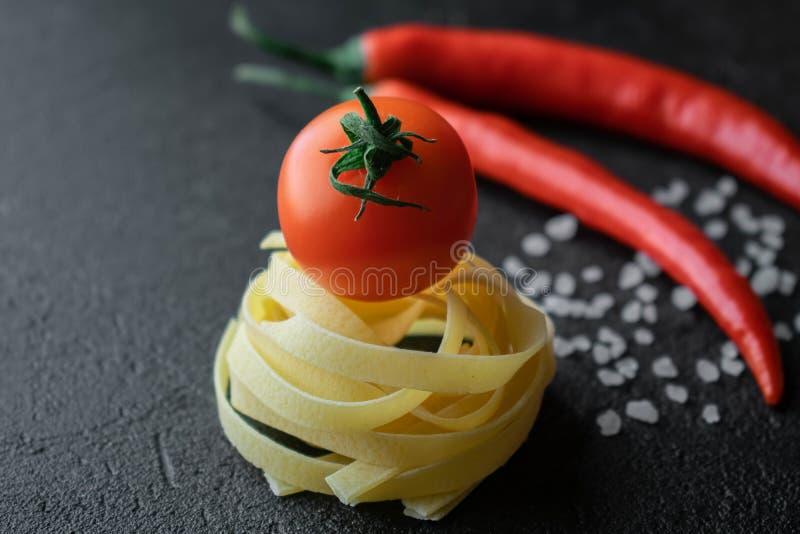 Pâtes crues de fettuccine avec la tomate fraîche, le sel brut de mer et les poivrons de piment photos stock