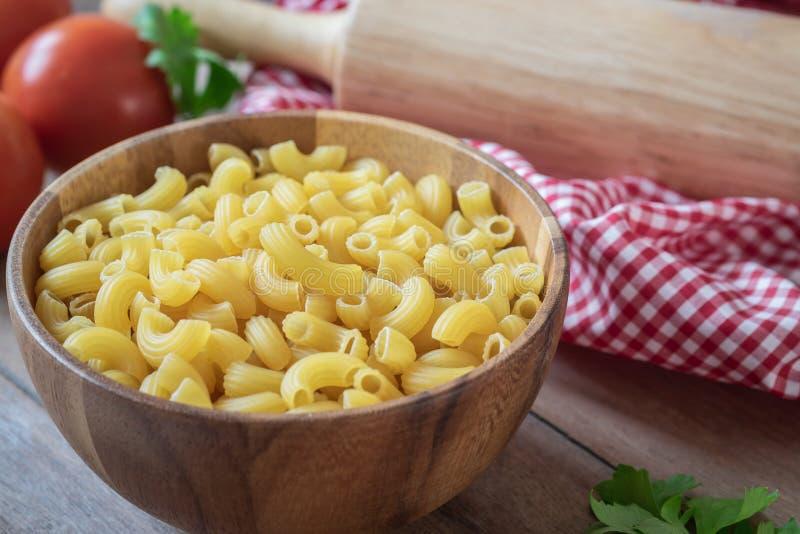 Pâtes crues de macaronis dans la cuvette en bois images stock