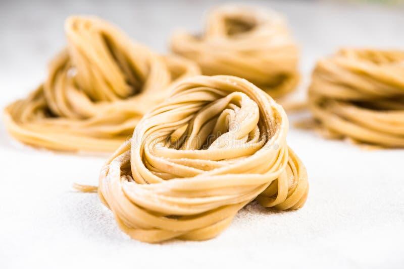 Pâtes crues de spaghetti italiens sur la table de marbre blanche images stock