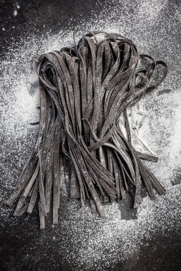 Pâtes crues faites maison de tagliatelles d'encre noire de calmar photo libre de droits