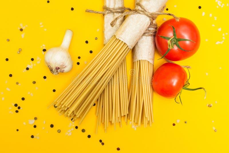 Pâtes crues sur un fond jaune dans un paquet rustique Tomates, ail, poivre et sel Vue supérieure image libre de droits
