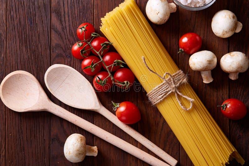 Pâtes crues, tomates sur le fond en bois, vue supérieure, plan rapproché, foyer sélectif photographie stock libre de droits