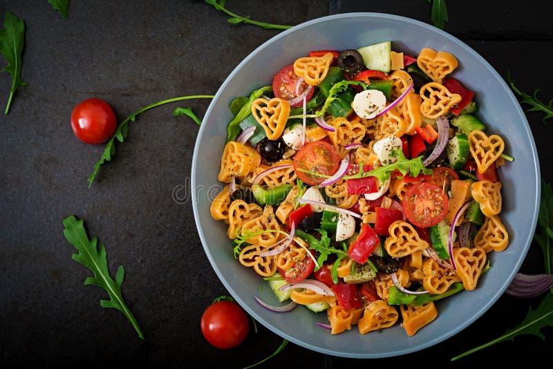 Pâtes dans la salade de coeur de forme avec le style de Grec de tomates, de concombres, d'olives, de mozzarella et d'oignon rouge images libres de droits