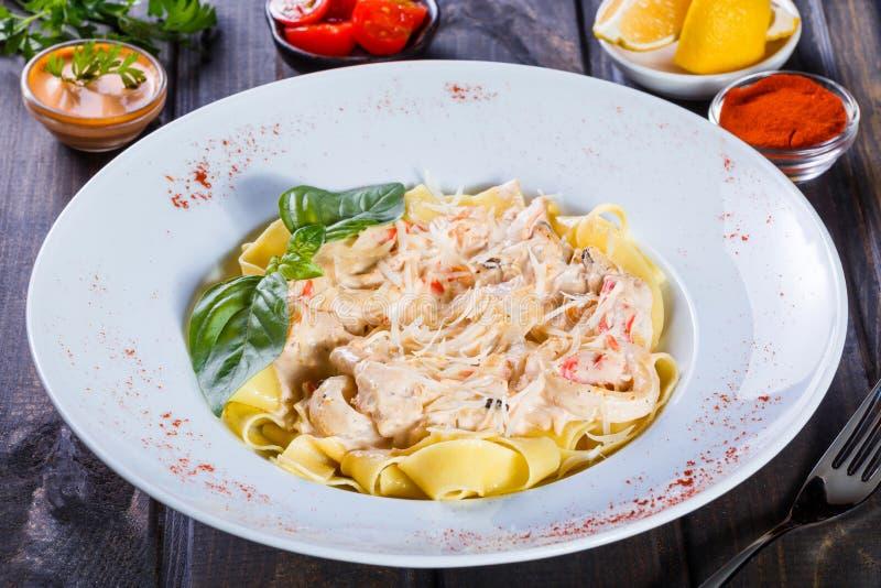 Pâtes de Fettuccine avec des fruits de mer, des anneaux de calmar, la crevette, des moules, des huîtres, la tomate, le parmesan,  photos stock