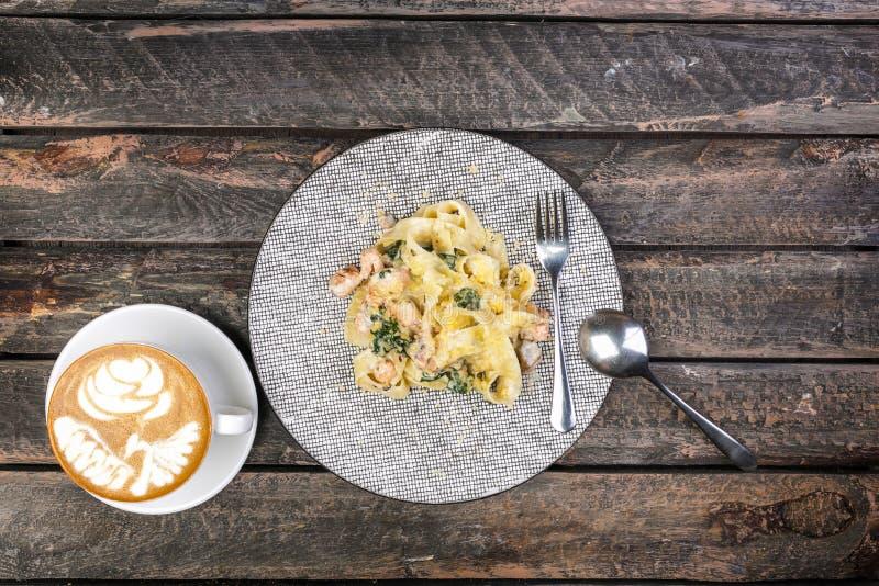 Pâtes de Fettuccine avec des fruits de mer dans la vieille vue supérieure en bois de table Servi avec des couverts et une tasse d photos libres de droits