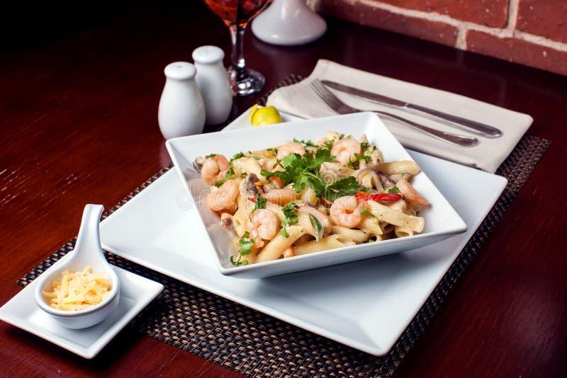 Pâtes de Penne avec des crevettes/crevettes roses et la saucisse en sauce tomate de pomodoro - cuisine italienne, faisant cuire,  image stock