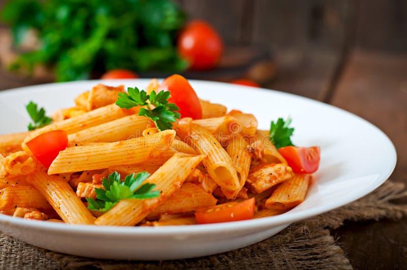 Pâtes de Penne en sauce tomate avec le poulet, tomates décorées du persil images libres de droits
