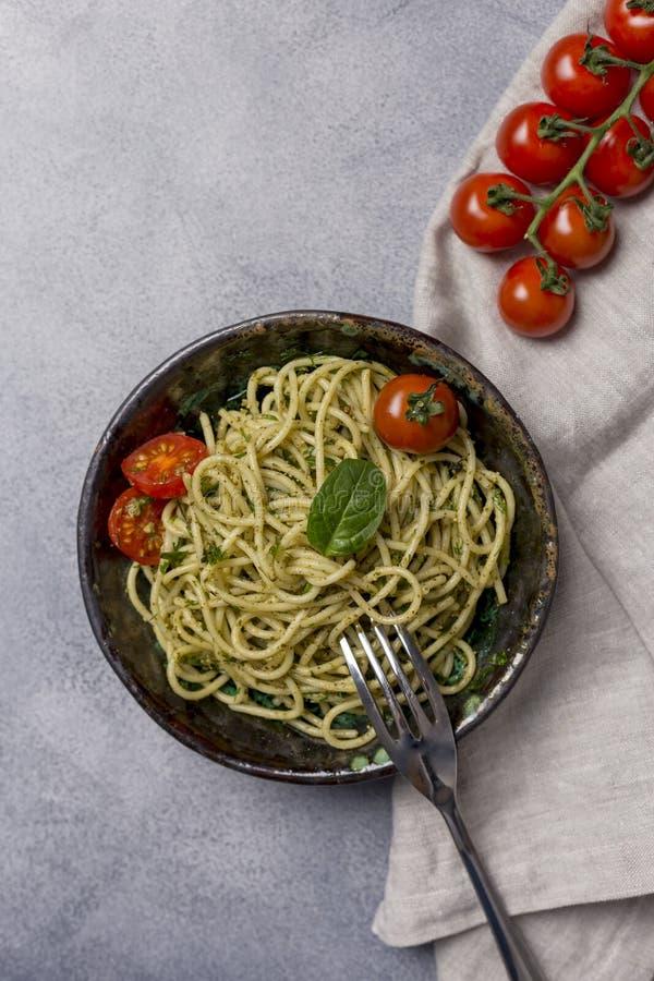 Pâtes de pesto avec des tomates dans la cuvette foncée au fond gris image libre de droits