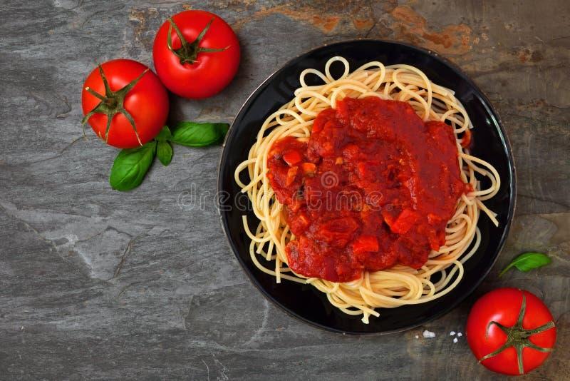 Pâtes de spaghetti avec la sauce tomate, les poivrons et les champignons, au-dessus de la vue sur un fond en pierre foncé photographie stock