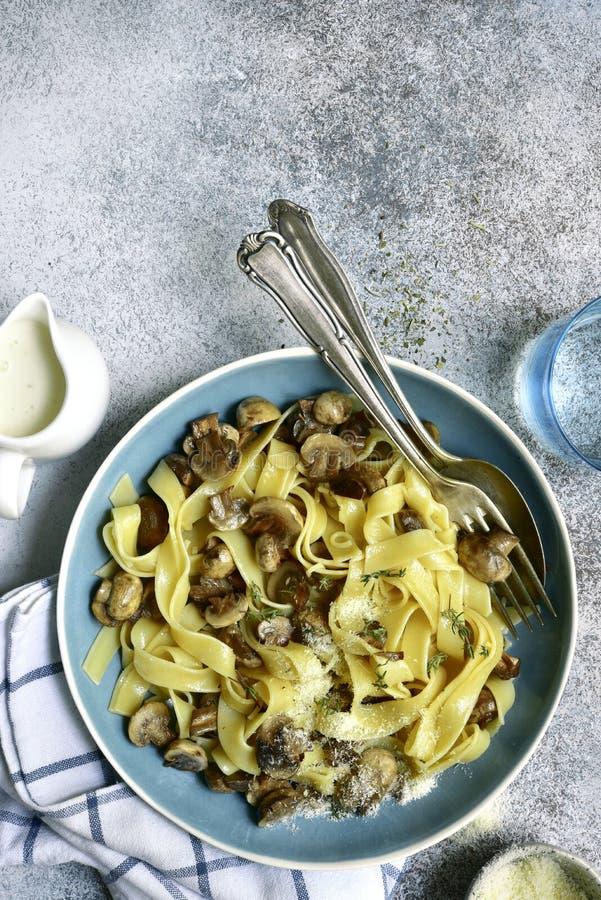 Pâtes de tagliatelles avec les champignons et le thym frits à une sauce crème Vue sup?rieure avec l'espace de copie images stock