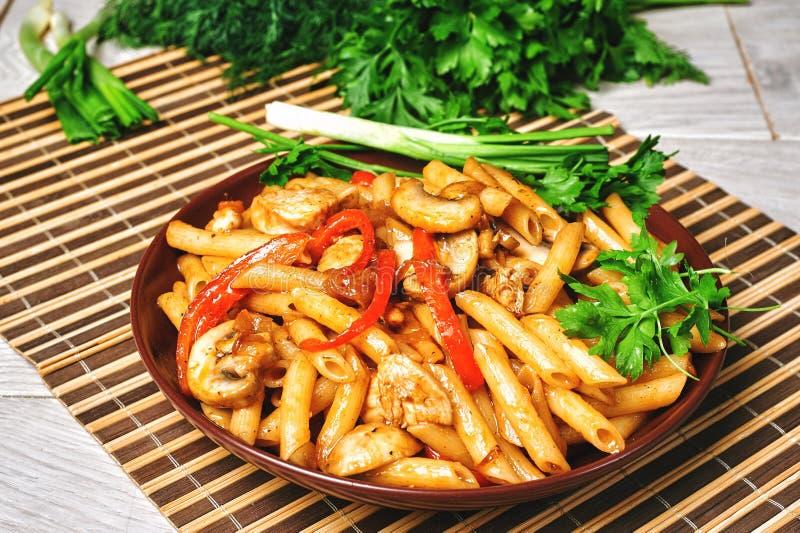 Pâtes en sauce tomate avec le poulet, champignons décorés du persil sur une table en bois photo libre de droits