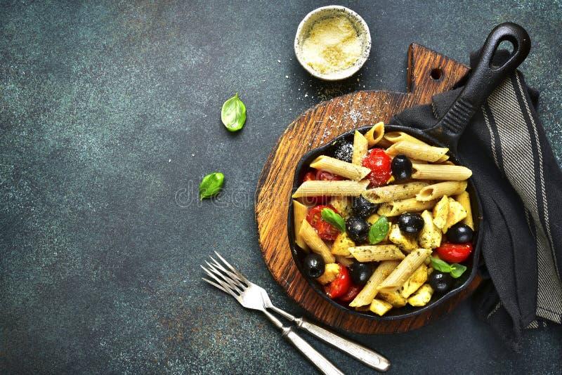 Pâtes entières de grain avec la cerise de tomate, les olives noires et le poulet À photo stock