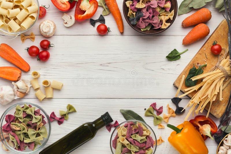 Pâtes et légumes italiens mélangés sur le bois blanc, vue supérieure image stock