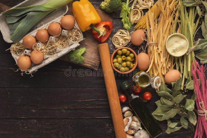 Pâtes et légumes italiens mélangés sur le bois foncé, vue supérieure photo stock