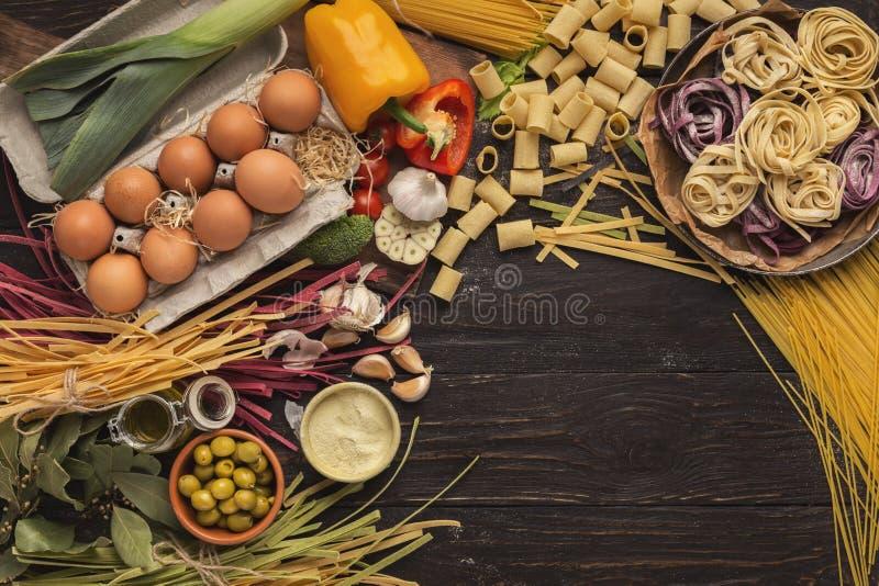 Pâtes et légumes italiens mélangés sur le bois foncé, vue supérieure image stock