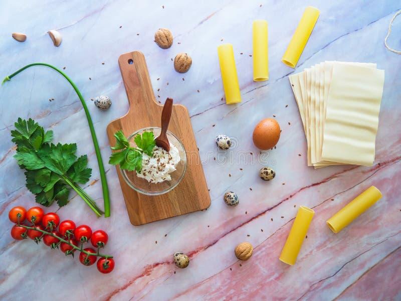 Pâtes et lasagne de Cannoli faisant cuire le concept Ingrédients sur une surface de marbre avec une planche à découper en bois images stock
