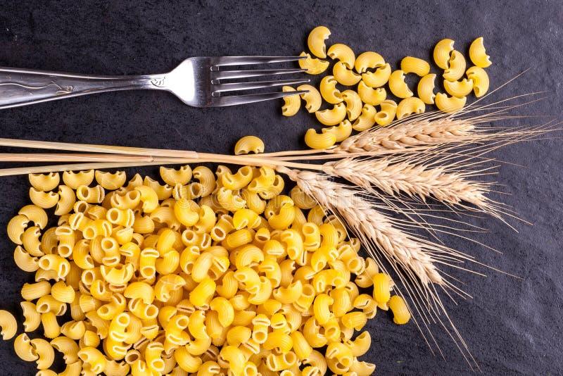 Pâtes et oreilles crues de blé photos stock