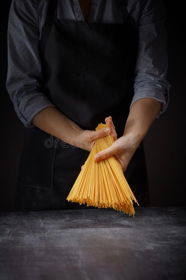Pâtes faites maison crues italiennes fraîches dans des mains femelles sur le fond foncé photographie stock libre de droits