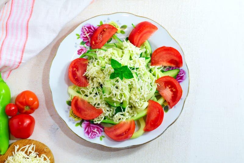 Pâtes faites maison de Zoodles de nouilles de courgette avec les tomates et le fromage sur le fond en bois blanc photo stock