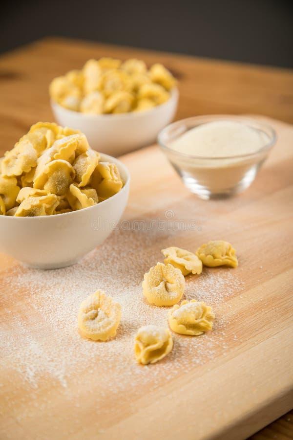 Pâtes fraîches et crues de Tortellini de Cappelletti d'Italien avec de la farine et semoule dans la cuvette de porcelaine et sur  photographie stock