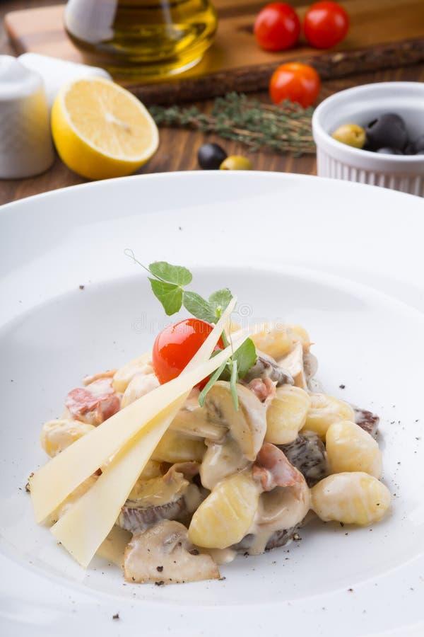 Pâtes italiennes avec du fromage et des champignons servis avec des tomates-cerises images libres de droits