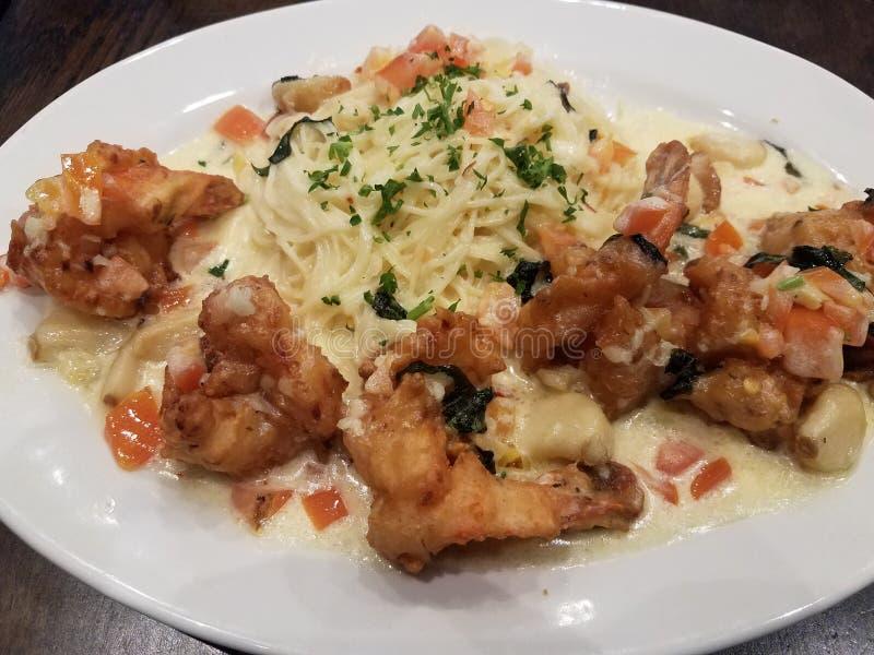Pâtes italiennes avec la crevette et la sauce frites avec l'ail et la tomate images stock