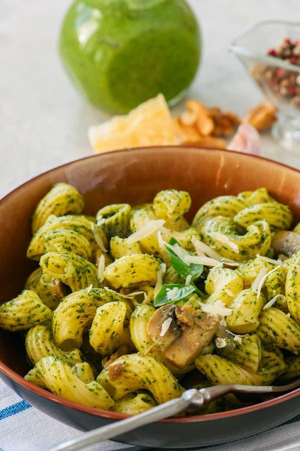 Pâtes italiennes avec le pesto de basilic et herbes dans un plat sur un s blanc photos libres de droits