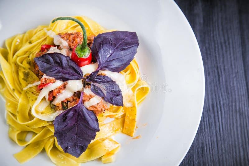 Pâtes italiennes dans un plat dans un restaurant avec des piments images stock