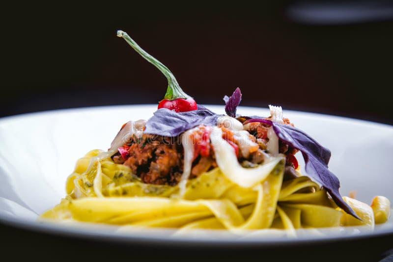 Pâtes italiennes dans un plat dans un restaurant avec des piments image libre de droits