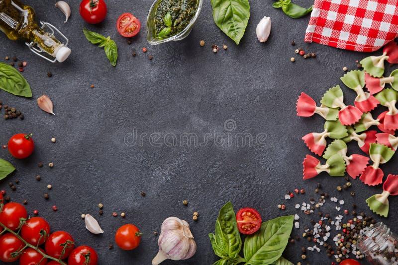 Pâtes italiennes de farfalle de drapeau Tomates-cerises, ail, basilic, pesto, huile d'olive, préparation de poivre, sel et servie photos stock