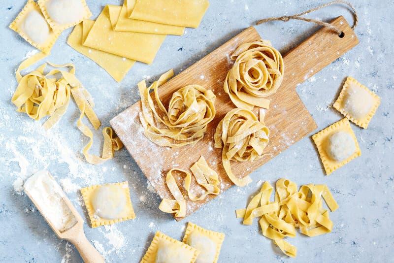 Pâtes italiennes faites maison, ravioli, fettuccine, tagliatelles sur un conseil en bois et sur un fond bleu Le procédé de cuisso images stock