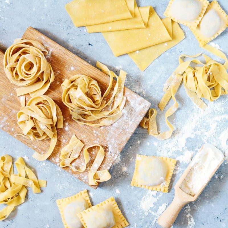 Pâtes italiennes faites maison, ravioli, fettuccine, tagliatelles sur un conseil en bois et sur un fond bleu Le procédé de cuisso photos libres de droits