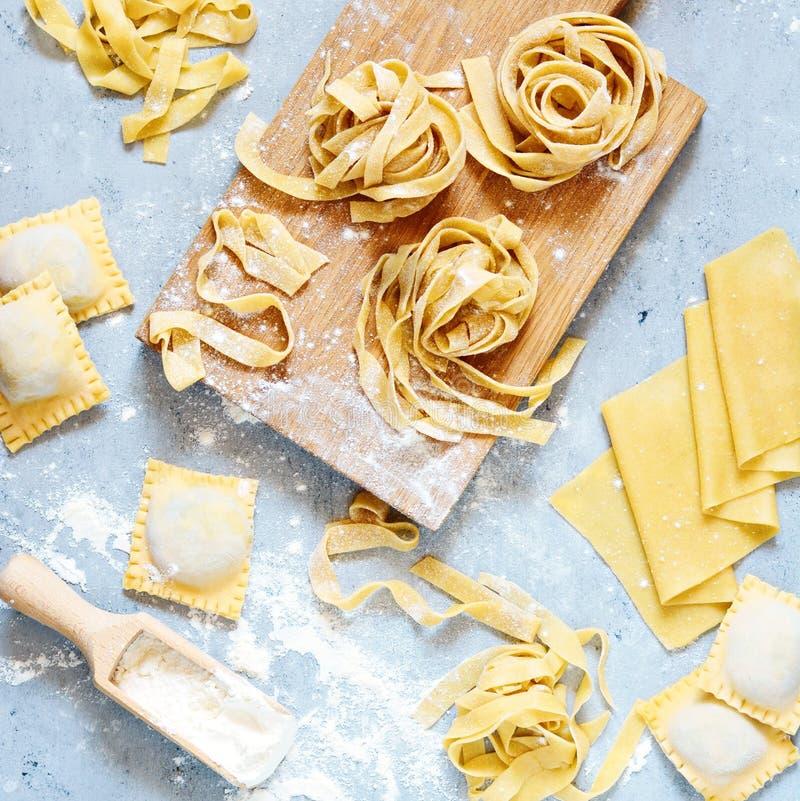 Pâtes italiennes faites maison, ravioli, fettuccine, tagliatelles sur un conseil en bois et sur un fond bleu Le procédé de cuisso photographie stock libre de droits