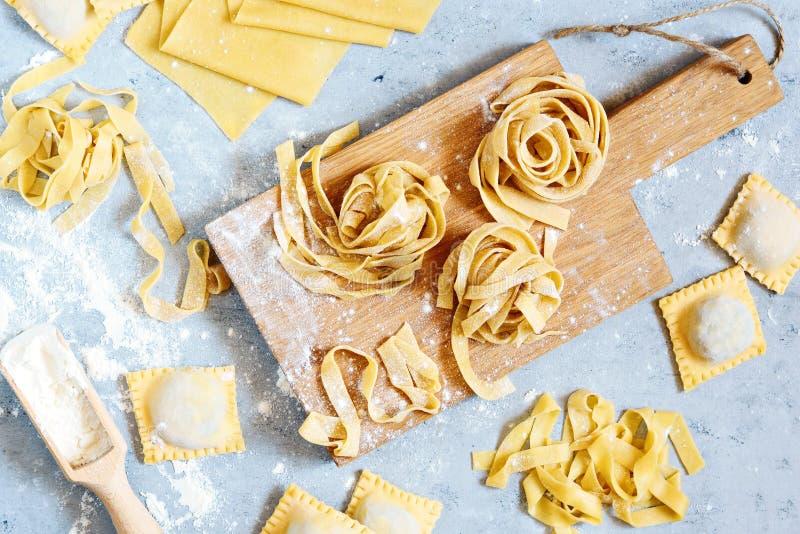 Pâtes italiennes faites maison, ravioli, fettuccine, tagliatelles sur un conseil en bois et sur un fond bleu Le procédé de cuisso photo libre de droits