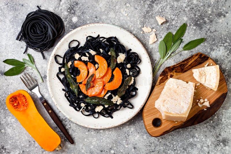 Pâtes noires avec la courge de butternut rôtie, le parmesan et la sauge frite Concept noir et orange de Halloween de partie de dî photographie stock