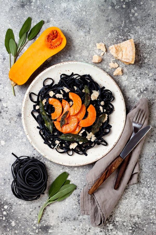 Pâtes noires avec la courge de butternut rôtie, le parmesan et la sauge frite Concept noir et orange de Halloween de partie de dî photos stock