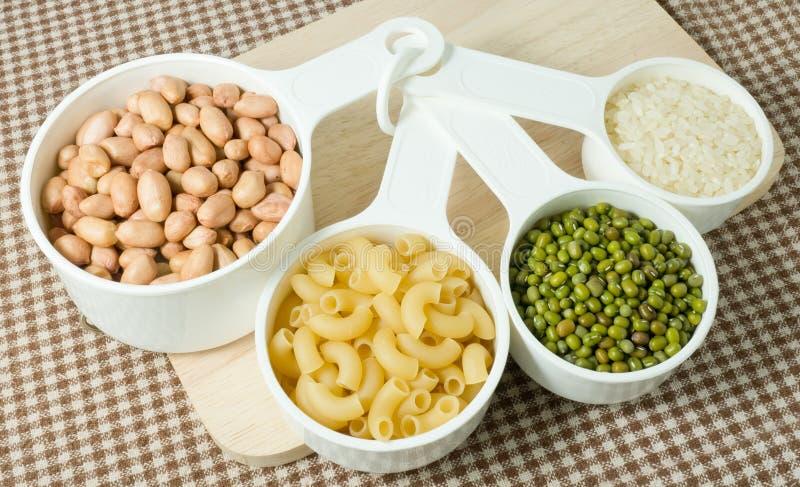 Pâtes, riz, arachides et fèves de mung dans des doseurs photographie stock libre de droits