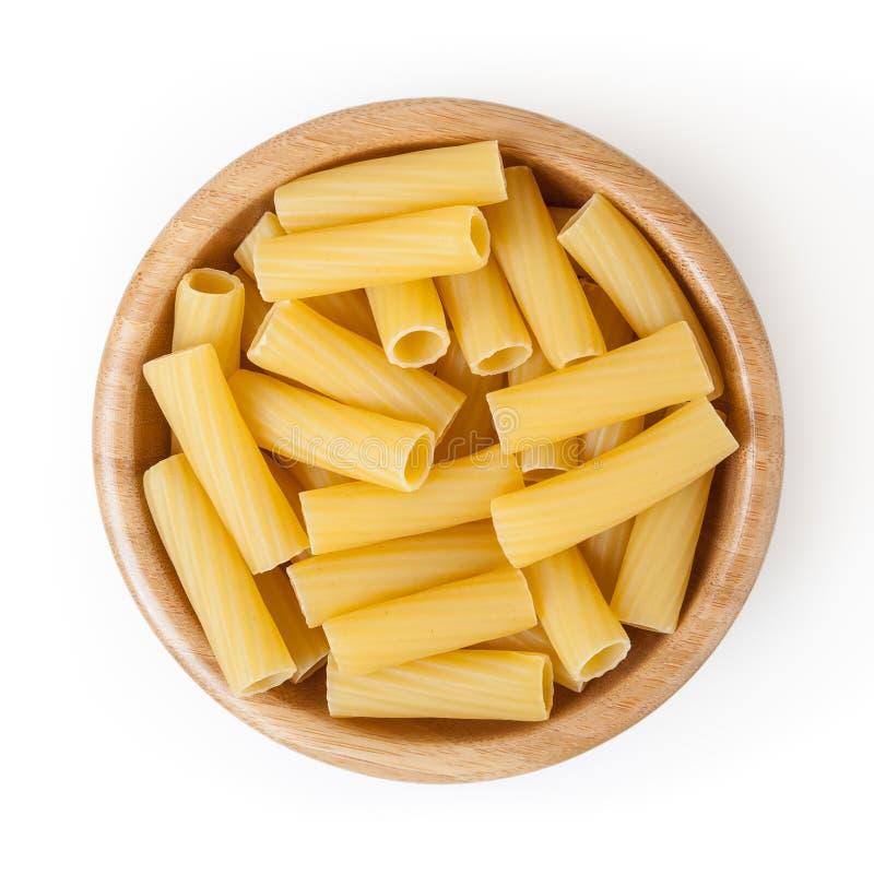 Pâtes sèches de tortiglioni dans la cuvette en bois d'isolement sur le blanc photos libres de droits